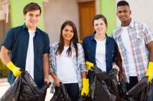 teenage volunteers with garbage bag