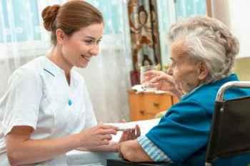 vroulike verpleegkundige gee senior vrou mediese pille