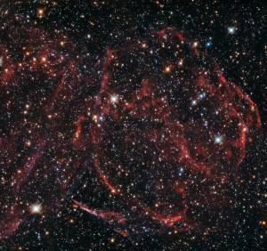 This NASA/ESA Hubble Space Telescope image captures the remnants of a long-dead star. These rippling wisps of ionised gas, named DEM L316A, are located some 160 000 light-years away within one of the Milky Way's closest galactic neighbours — the Large Magellanic Cloud (LMC). The explosion that formed DEM L316A was an example of an especially energetic and bright variety of supernova, known as a Type Ia. Such supernova events are thought to occur when a white dwarf star steals more material than it can handle from a nearby companion, and becomes unbalanced. The result is a spectacular release of energy in the form of a bright, violent explosion, which ejects the star's outer layers into the surrounding space at immense speeds. As this expelled gas travels through the  interstellar material, it heats it up and ionise it, producing the faint glow that Hubble's Wide Field Camera 3 has captured here. The LMC orbits the Milky Way as a satellite galaxy and is the fourth largest in our group of galaxies, the Local Group. DEM L316A is not alone in the LMC; Hubble came across another one in 2010 with SNR 0509 (heic1018), and in 2013 it snapped SNR 0519 (potw1317a).