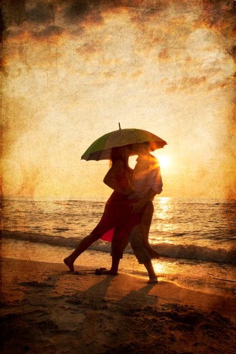 Couple kissing under umbrella at the beach in sunset. Photo in the