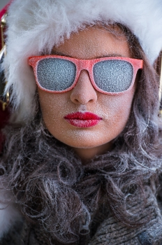 Woman wearing Santa Claus hat and sunglasses listening to music